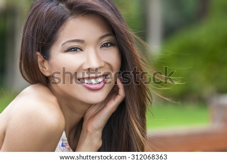 Outdoor portrait of a beautiful young Chinese Asian young woman or girl with perfect teeth, smiling and resting in her hand