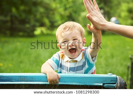 outdoor portrait of a boy on green background. happy child on walk in the summer park. Give five gesture support. high five #1081298300
