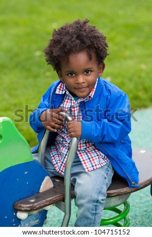 Outdoor portrait of a cute  black baby boy playing at playground