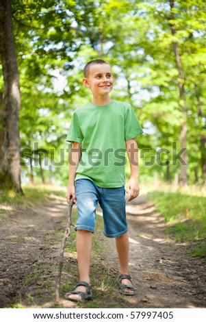 Outdoor portrait of a cute child walking through the forest carrying a stick