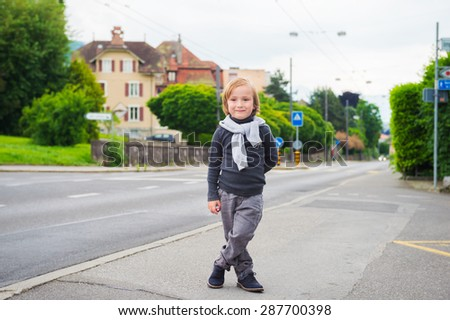 Outdoor portrait of a cute fashion boy in the street, wearing, grey clothes and dark blue shoes