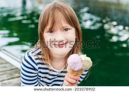 Outdoor portrait of a cute little girl, eating ice cream in a port