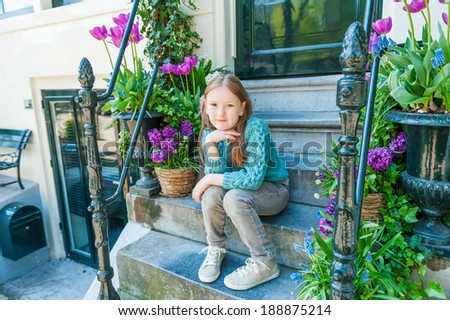 Outdoor portrait of a cute little girl sitting on steps in a city on a nice spring day