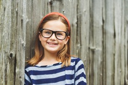 Outdoor portrait of a cute little 9 year old girl wearing eyeglasses