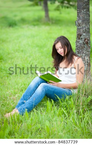 Outdoor portrait of a cute teen sitting under a tree and reading a book - stock photo