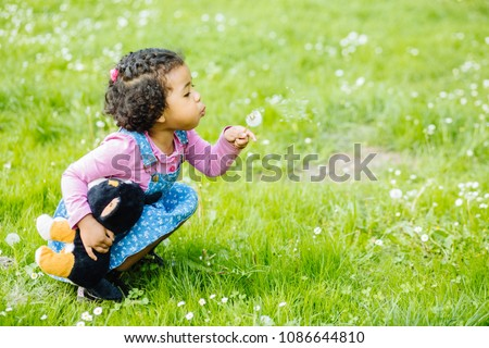 Outdoor portrait of a cute toddler black girl blowing a dandelion flower - African american or mexican ethnicity concept. #1086644810