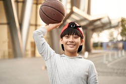 outdoor portrait of a happy fifteen-year-old asian teenage basketball player