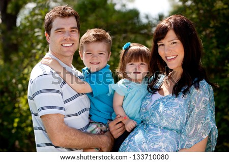 Outdoor portrait of a happy young family with pregnant mother