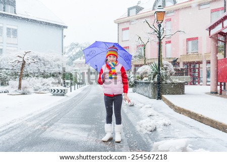 Outdoor portrait of a pretty little girl in a city under the snowfall