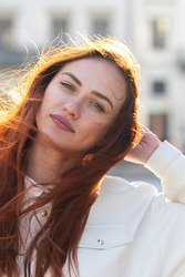 Outdoor portrait of a red-haired young woman in a white shirt. Sun glare, soft focus.