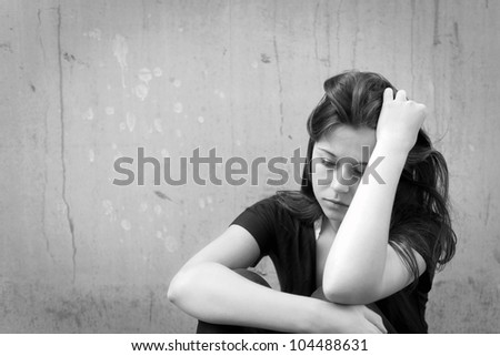 Outdoor portrait of a sad teenage girl looking thoughtful about troubles, monochrome photo