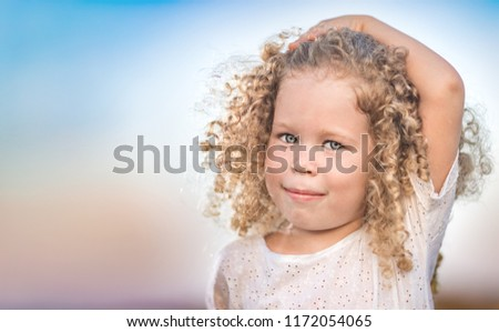 Outdoor portrait of a smiling little girl. Positive emotion concept.