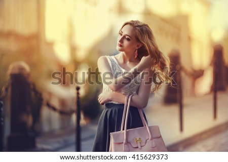 Outdoor portrait of a young beautiful fashionable lady walking on street. Model wearing stylish clothes. Girl looking aside. Female fashion. City lifestyle. Toned style instagram filters