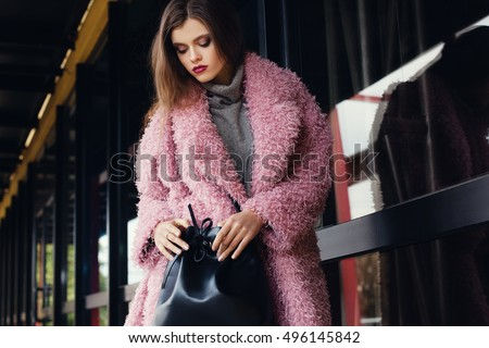 Outdoor portrait of a young beautiful fashionable lady walking on the street. Model wearing stlysh clothes. Girl looking in her bag. Waist up #496145842
