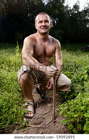 Outdoor portrait of a young farmer in a potato lawn - stock photo