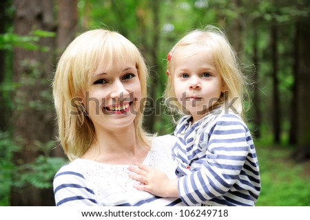 Outdoor portrait of a young mother posing with her daughter in the park