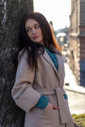 Outdoor portrait of a young woman near a tree. Brunette in a gray coat. Sun glare, soft focus.