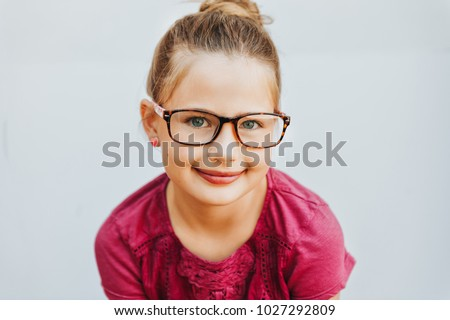 Outdoor portrait of adorable kid girl wearing glasses #1027292809