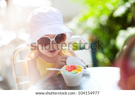 Outdoor portrait of adorable little girl eating ice cream