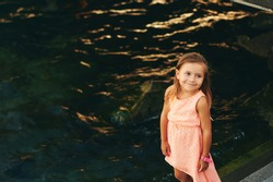 Outdoor portrait of adorable 3 or 4 year old little girl by the river or lake, water background