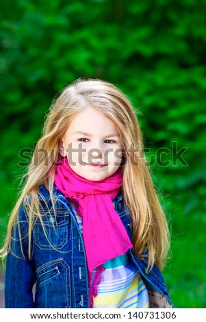 Outdoor portrait of an adorable smiling blond little girl wearing a blue jeans jacket and a pink scarf