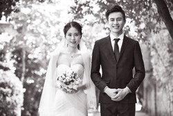 outdoor portrait of asian bride and groom looking at camera smiling, black and white.