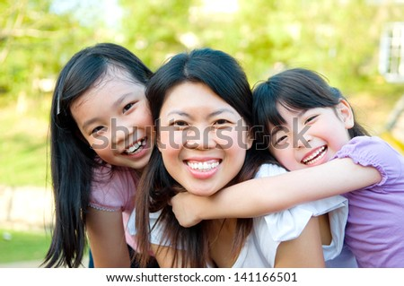 Outdoor portrait of asian mother and her lovely daughters
