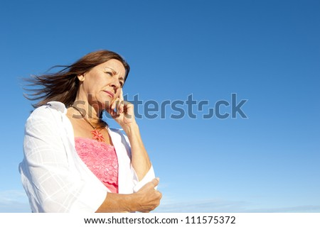Outdoor portrait of attractive mature  woman looking depressed, worried, tired, isolated with blue sky as background and copy space.