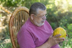 Outdoor portrait of  bearded Caucasian senior farmer sitting in whicker chair and watching on ripe melon in hands