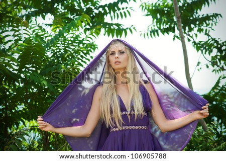 Outdoor portrait of beautiful blond woman in purple dress with veil