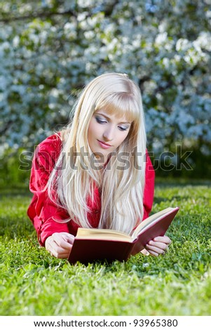 outdoor portrait of beautiful blonde girl student lying on green grass near bloomin tree and reading book