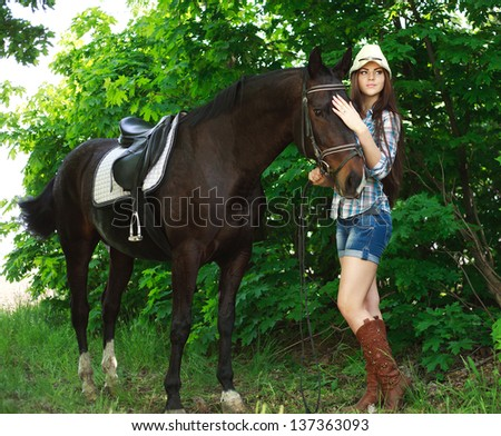 Outdoor portrait of beautiful cowgirl with horse in the green forest