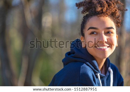 Outdoor portrait of beautiful happy mixed race biracial African American girl teenager female young woman smiling with perfect teeth wearing a blue hoodie Stockfoto ©