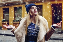 Outdoor portrait of beautiful happy smiling young woman posing on street. Model looking up, at sky. Lady wearing stylish winter clothes. Magic snowfall effect. Christmas, new year concept. Waist up