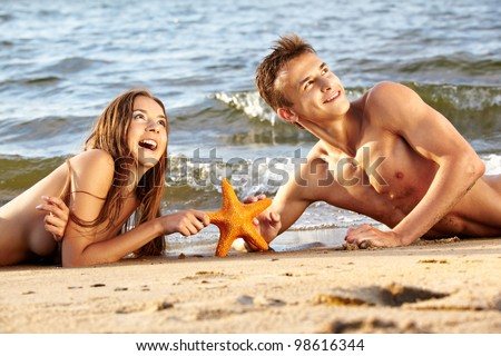outdoor portrait of beautiful romantic couple of topless girl and muscular guy in jeans laying face to face with asteroid on beach