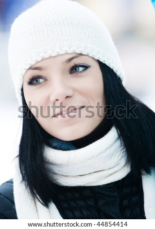 Outdoor portrait of beautiful smiling young girl with white cap and scarf