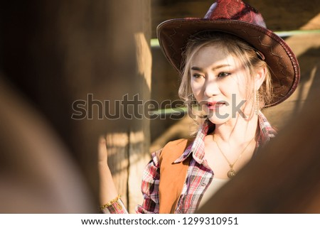 Outdoor portrait of beautiful young asian woman dressed as like a cowgirl at sunset time.Thailand