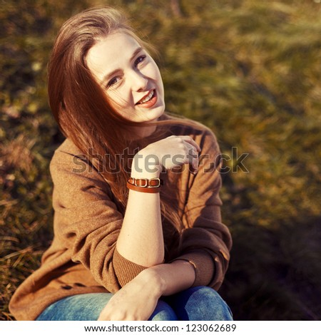Outdoor portrait of beautiful young brunette in spring in the park.