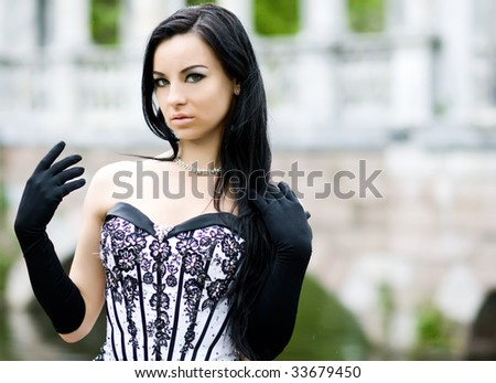 Outdoor portrait of beautiful young girl in stylish dress