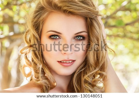 Outdoor portrait of beautiful young woman against sunny forest