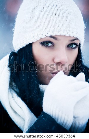 Outdoor portrait of beautiful young woman with white cap and scarf
