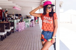 Outdoor portrait  of brunette girl in stylish swag  pink cap ,trendy summer outfit posing in cafe, enjoying summer vacations. Sunglasses.