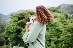 Outdoor portrait of curly european tanned woman holds happy pet dog pomeranian spitz. Silver bracelet on hand. Spending time with lovely white fluffy puppy. Happy moments with pets. Exotic background.
