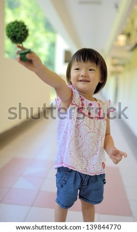 Outdoor portrait of cute little girl holding a plant