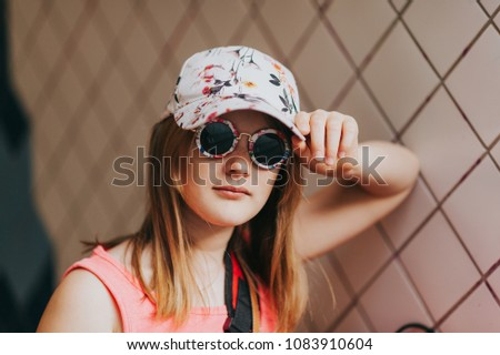ae023054a063 Outdoor portrait of cute little preteen girl wearing fashion cap and  sunglasses #1083910604