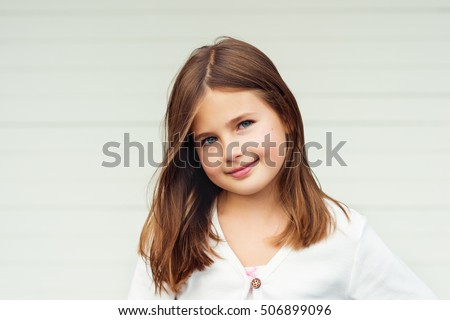 Outdoor portrait of cute little 8-9 year old girl with brown hair, wearing white jacket, standing against white background Stock photo ©