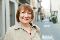 Outdoor portrait of european mature woman in old city street