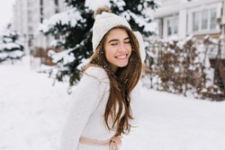 Outdoor portrait of fascinating brunette lady posing with romantic smile on snowy background. Photo of pretty laughing girl in knitted hat and soft sweater on the winter street.