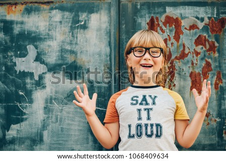 "Outdoor portrait of funny little boy wearing glasses and t-shirt with sign ""Say It Loud"""