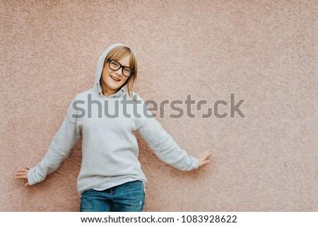 c9e557756364 Outdoor portrait of funny little girl wearing grey sweatshirt posing  against pink background #1083928622